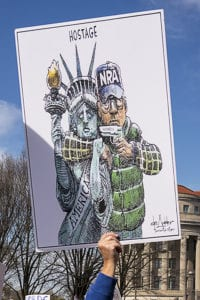 Sign showing an NRA gunman holding the Statue of Liberty hostage