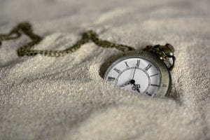 Stopwatch half buried in sand
