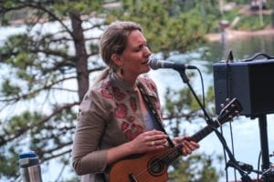 Photo of Victoria Vox playing in front of a pine tree and a lake