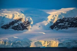 Photo of a mountain side in Antarctica with massive glaciers on top the mountains and flowing down to the sea