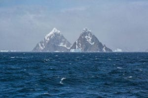Photo of the South Shetland Islands in Antarctica, two triangular-shaped tall mountain peaks