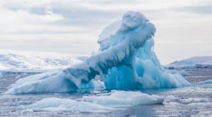 Photo of a twisted blue iceberg shaped by the sea and the wind.