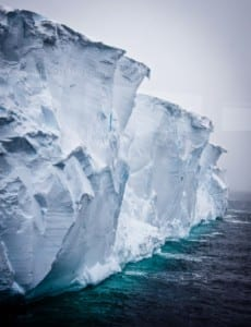 Photo of a large tabular iceberg with blue ice at the water line