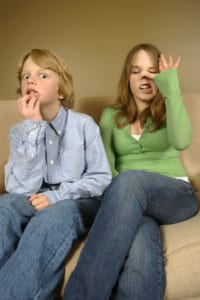 Photo of a boy and girl clowning on a sofa