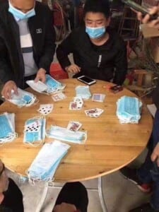 Men playing poker using face masks as chips