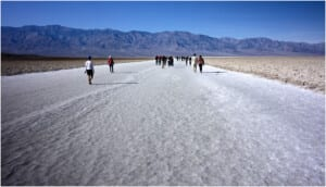 Photo of hikers walking down a long, white road in Badwater Basin
