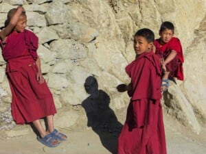 Photo of three young novice monks in red robes