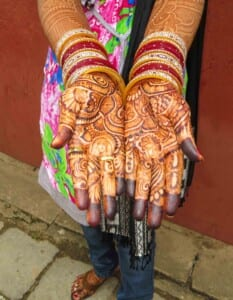 Photo of a woman's hands with elaborate henna tattoos on her palms