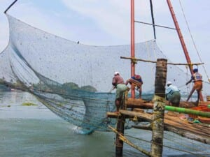 Photo of men on a fishing boat hauling in the net