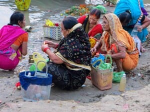 Photo of four women sitting on the banks of the Ganges River