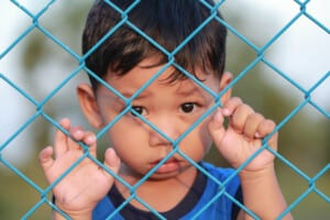 Photo of a small Latino boy behind a metal fence