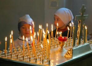 Two girls lighting candles at a church