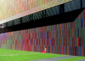Photo of a student sitting beneath a wall at Munich's modern art museum