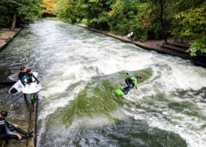Photo of young men surfing on a river in Munich