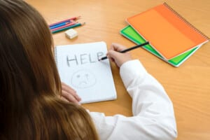 """Photo of a girl writing """"help"""" on paper"""